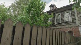 Mening van oud geschermd houten Russisch huis met groene boom naast stock video
