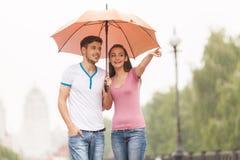 Mening van paar onder paraplu die in de herfst lopen Stock Foto's