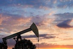 Mening van pumpjack pompende olie bij zonsondergang royalty-vrije stock afbeeldingen