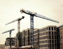 Mening van reuzekranen op een achtergrond van moderne gebouwen in aanbouw Stock Fotografie