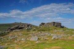 Mening van Rowtor met de Piek van de het Westenmolen op de achtergrond met witte wolken in een blauwe hemel, Dartmoor Royalty-vrije Stock Foto's