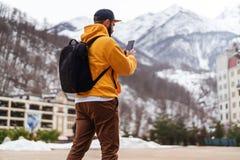 Mening van rug De mensentoerist in gele hoodie, GLB met rugzak bevindt zich op achtergrond van hoge sneeuwbergen en het gebruiken stock foto's