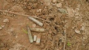 Mening van shell omhulsel van Duits machinegeweer MG-42б, van pistool en geweer op grond in bos stock video