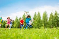 Mening van snel bewegende jongen die wit vliegtuigstuk speelgoed houden royalty-vrije stock foto