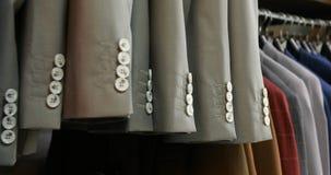 Mening van sommige identieke jasjes op hangers in winkel stock footage