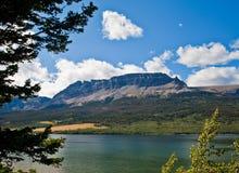 Mening van St Mary Lake door Bomen Stock Fotografie