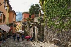 Mening van steeg in helling, gebouwen en muur met winde in Bellagio Stock Foto