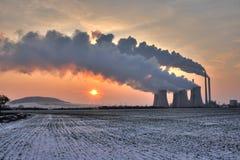 Mening van steenkoolkrachtcentrale tegen zon en reusachtige dampen stock fotografie