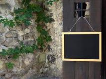 Mening van steenmuur, installatie en houten donkere deur Stock Afbeeldingen
