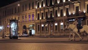 Mening van straat met kruispunt, het advertentiescherm en tweepersoons op paarden nacht stock footage