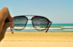 Mening van strandstrand, overzees en jacht over glazen Stock Foto's