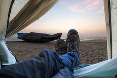 Mening van tenten op een zandig strand door het overzees en een boot bij zonsondergang Reizen en expedities in de wildernis Conce royalty-vrije stock afbeeldingen