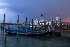 Mening van traditionele Gondels op Kanaal Grande met de kerk van Basiliekdi Santa Maria della Salute een bewolkte avond Venetië,  Stock Foto