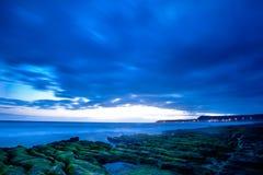 Mening van tropisch rotsachtig strandlandschap bij zonsopgang Royalty-vrije Stock Afbeelding