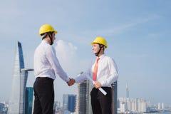 Mening van Twee arbeiders die buiten met een tablet aan een bouwwerf werken stock foto