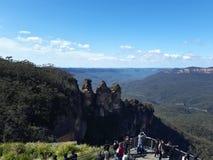 Mening van vallei en bergen en Drie Zusters met eucalyptusbomen op een duidelijke blauwe hemeldag in Jamison Valley NSW Australië stock afbeelding