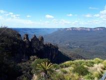 Mening van vallei en bergen en Drie Zusters met eucalyptusbomen op een duidelijke blauwe hemeldag in Jamison Valley NSW Australië stock afbeeldingen