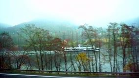Mening van venster die van het overgaan van trein door rivier en bergen in de herfst overgaan stock videobeelden