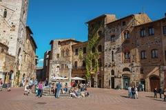 Mening van vierkant met mensen, oude gebouwen in San Gimignano stock afbeeldingen