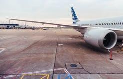 Mening van vliegtuigvleugel en motor op tarmac bij luchthaven stock foto