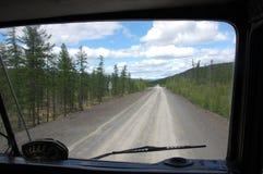 Mening van vrachtwagen aan het binnenland Rusland van Kolyma van de grintweg Stock Fotografie