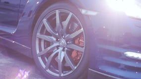 Mening van wielenschijf van donkerblauwe nieuwe auto presentatie koplampen Zon auto Koude schaduwen stock footage