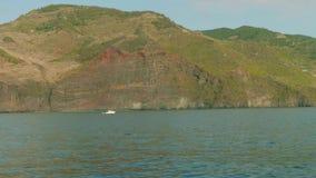 Mening van witte vissenboot die langs de rotsachtige kust van Madera varen stock video