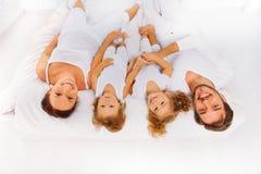 Mening vanaf bovenkant van moeder, vader, twee jonge geitjes op bed Stock Afbeelding