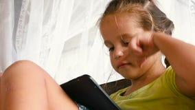 Menings Kaukasisch Meisje in Bed Leren, die op Tablet in Slaapkamer spelen stock videobeelden