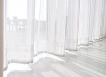 meningszeegezicht die gordijnen van de pas de Doorzichtige witte stof kijken en stock foto