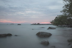 Meningszonsondergang op het rotsachtige strand wanneer vloed stock afbeeldingen