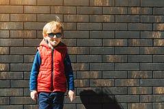 Menino à moda bonito contra a parede de tijolo fora Menino elegante louro nos óculos de sol, na veste vermelha vestindo, olhando  fotografia de stock