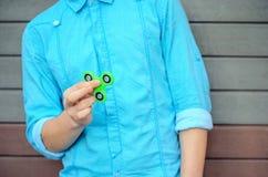 Menino à moda de Yong na mão que guarda a rotação popular da inquietação do dispositivo fotografia de stock royalty free