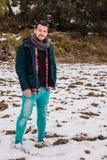 Menino à moda, mãos em seus bolsos E no fundo um prado com neve imagem de stock