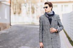 Menino à moda nos óculos de sol no revestimento com a pasta na rua imagens de stock royalty free