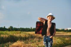 Menino à moda vestido no campo com mala de viagem Foto de Stock