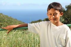 Menino étnico novo ao ar livre na luz do sol do campo Foto de Stock