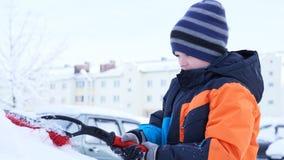 Menino adolescente adorável que ajuda a escovar uma neve de um carro foto de stock