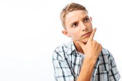 Menino adolescente bonito que levanta, retrato ascendente próximo, guardando a mão na frente da cara, no estúdio no fundo branco imagem de stock