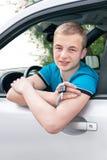 Menino adolescente caucasiano que mostra a chave nova do carro e o carro Imagens de Stock
