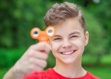 Menino adolescente com o brinquedo do girador no parque Imagem de Stock Royalty Free