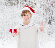 Menino adolescente com o chapéu de Santa e as caixas de presente vermelhas que mostram os polegares acima Foto de Stock