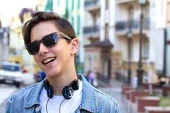 Menino adolescente com os fones de ouvido da música no fundo urbano Imagem de Stock Royalty Free