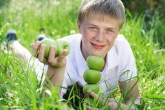 Menino adolescente com a pirâmide das maçãs verdes que encontram-se sobre Fotos de Stock Royalty Free