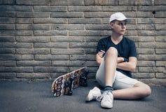 Menino adolescente com skate na frente de uma parede de tijolo Imagens de Stock