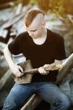 Menino adolescente com uma pá como uma guitarra em suas mãos Awkwa difícil fotografia de stock