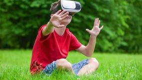 Menino adolescente com vidros de VR no parque video estoque