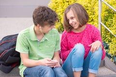 Menino adolescente e menina com fones de ouvido imagem de stock