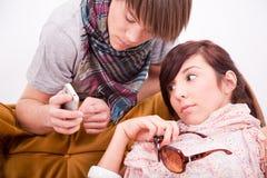 Menino adolescente e menina com um telefone Fotos de Stock Royalty Free