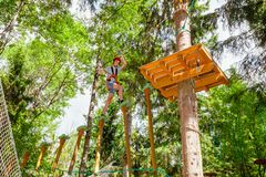 Menino adolescente em um curso das cordas em um parque da aventura da copa de árvore que passa o obstáculo da corda de suspensão foto de stock